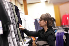 Woman in clothes shop Stock Images
