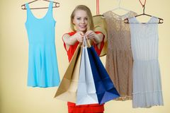 Woman in shop picking summer outfit. Woman in clothes shop store holding shopping bags picking summer perfect outfit, dress hanging on clothing hangers stock image