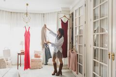Woman with clothes in sunny room Royalty Free Stock Photography