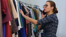 Woman in clothing shop talking with friend with mobile phone and choosing a new dress stock video