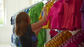 Woman in the clothing store is considering clothes stock footage