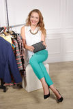 Woman in a clothing store showing her purse Stock Image