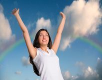 Woman  with clouds and rainbow behind her. Happy woman with hands in air with rainbow and clouds behind her Stock Images