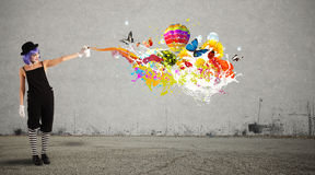 Woman clown with colored spray. Paints trails Royalty Free Stock Image