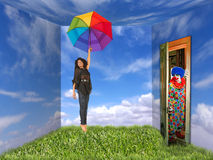 Woman and Clown in Landscape-Painted Room. A young woman holds a rainbow umbrella. She is in a room that is painted like an outdoor landscape and a clown is at Royalty Free Stock Image