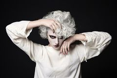 Woman with clown make-up for halloween. Young woman with scary clown make-up for halloween.blond girl with white skin wear straitjacket.psycho person for Royalty Free Stock Photo