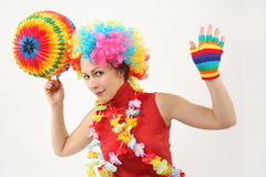 Woman in clown wig, flower garland and balls Stock Images