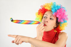 Woman in clown wig and party blower pointing left Royalty Free Stock Image