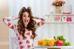 Woman clutched her head. Surprised blogger looking straight at the camera with opened mouth and standing near a table with fruits and vegetables stock photography