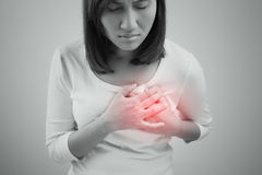 Woman is clutching her chest, acute pain possible heart attack Stock Image