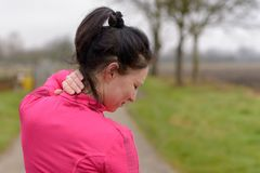 Woman clutching her neck in pain. While out exercising on a country road in winter in a close up cropped view royalty free stock image