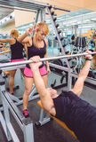 Woman coach encouraging to man in bench press Royalty Free Stock Images