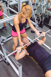 Woman coach helping to man in bench press training. Woman personal trainer helping to muscle men for a correct bench press training with barbell on fitness Stock Photography