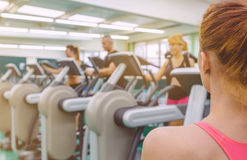 Woman coach looking people in elliptical trainer Stock Photography