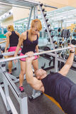 Woman coach screaming to man in bench press Stock Images