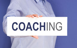 Woman with coaching sign. Body of businesswoman with coaching sign, blue background Stock Photos