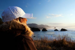 Woman at coast overlooking ocean royalty free stock photography