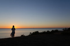 Woman by coast at sunset Stock Image