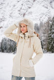 Woman in coat adjusting hat while standing in winter outdoors Royalty Free Stock Images