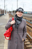Woman in coat and cap with red bag Royalty Free Stock Images