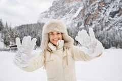 Woman in coat and fur hat showing snow-covered mittens outdoors. Magical mix of winter season and mountain landscape create the perfect mood. Closeup on snow Stock Photography