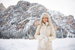 Woman in coat and fur hat wearing gloves while standing outdoors Royalty Free Stock Images