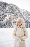Woman in coat and fur hat wearing gloves while standing outdoors. Magical mix of winter season and mountain landscape create the perfect mood. Happy young woman Stock Photos