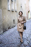Woman at coat with handbag at her minds Royalty Free Stock Image
