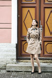 Woman at coat with handbag and old doors Royalty Free Stock Images