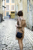 Woman at coat with handbag turned her back Stock Images