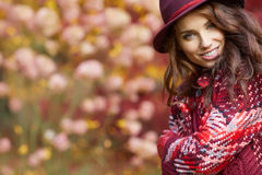 Woman in coat with hat and scarf in autumn park Stock Photos