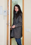 Woman in coat loocking door Royalty Free Stock Photography