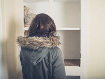 Woman in coat looking at old cupboard Royalty Free Stock Image