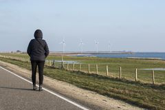 Woman in coat looking at the windmills Stock Image