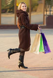 Woman in coat with multi-colored shopping bags Royalty Free Stock Photo