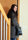 Woman in coat opening door Royalty Free Stock Photography