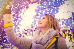 Woman in coat and scarf with Christmas time light royalty free stock images