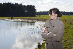 Woman in coat standing by a lake Royalty Free Stock Photography