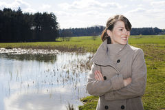 Woman in coat standing by a lake Stock Image