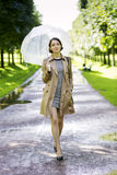 Woman at coat with umbrella at sunny day Royalty Free Stock Photography
