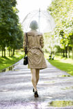 Woman at coat under umbrella walk in park Stock Image