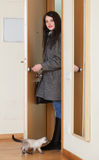 Woman in coat unlocking the door. And returned in home Royalty Free Stock Images