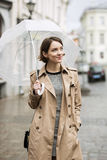Woman at coat on wet street after rain Royalty Free Stock Images