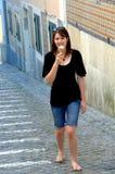 Woman on cobblestone street with ice cream cone. Woman walking along a historic cobblestone street in Lisbon with an ice cream cone stock images