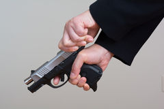 Woman cocking a hand gun Royalty Free Stock Photos
