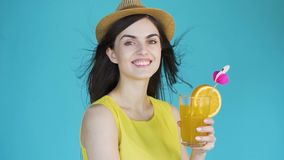 Woman with cocktail. Attractive brunette holding tasty cocktail with orange, wearing straw hat and yellow summer top, slowmotion in the aqua background, concept stock video footage