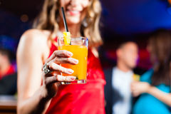 Woman with cocktail in bar or club Stock Photo