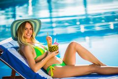 Woman with cocktail glass chilling near swimming pool on a deck chair. Portrait of young woman with cocktail glass chilling in the tropical sun near swimming royalty free stock images