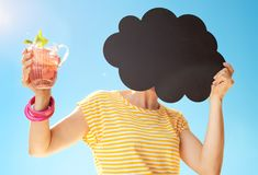 Woman with cocktail hiding behind cloud shaped blackboard Royalty Free Stock Photography
