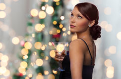 Woman with cocktail over christmas tree lights Stock Photos